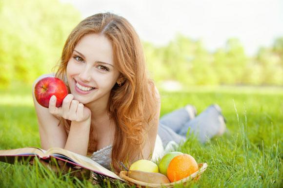 Девушка читает книгу с яблоком фото
