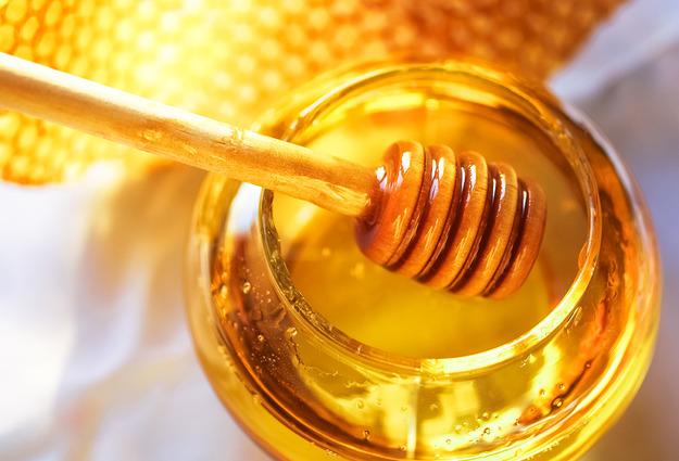 Фото продукта пчеловодства в банке ложечкой