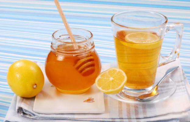 Мед в баночке и чай с лимоном в кружке фото
