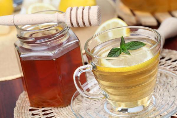 Фото банки с медом и прозрачной чашки с чаем