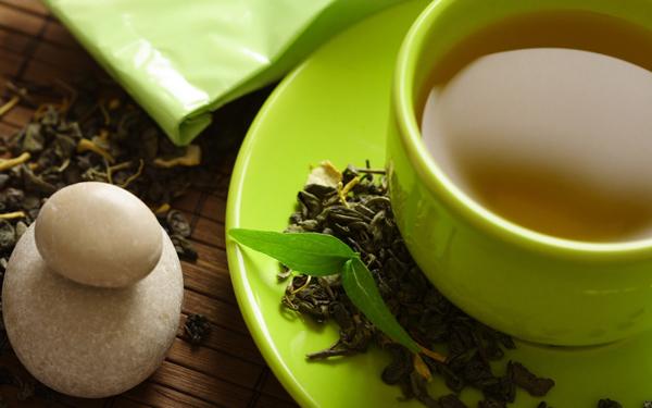 Фото чая в зеленой чашке и чайных листьев