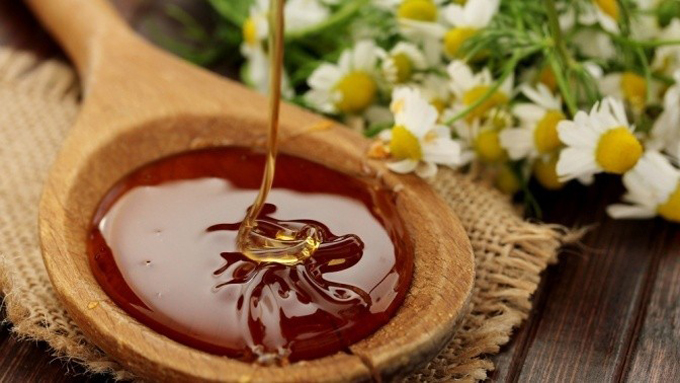 Фото деревянной ложки с лесным медом и ромашек