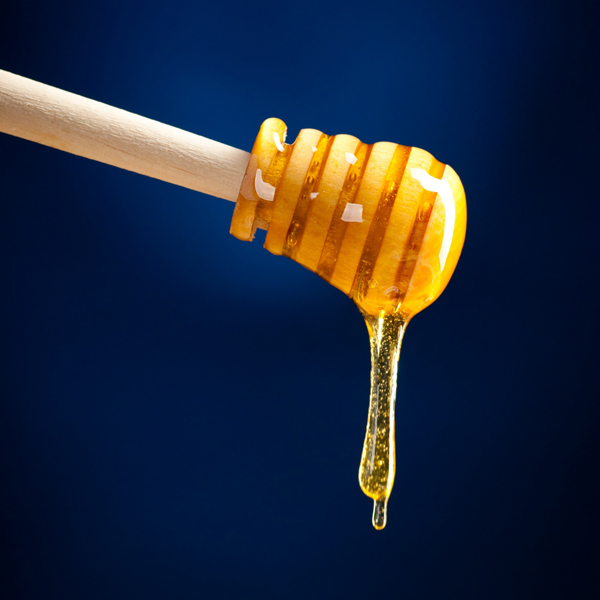 Фото капли меда, стекающей с деревянной ложки-колотушки