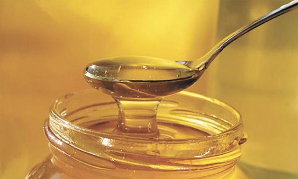 Фото меда, который зачерпнули ложкой из банки