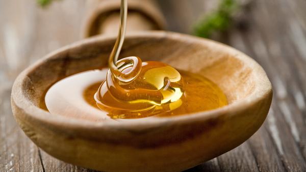 Фото оседающей горки меда в деревянной плошке