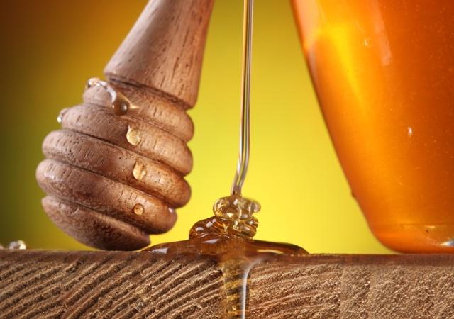 Фото струйки меда и деревянной ложечки
