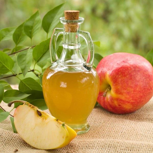 Фото уксуса в графине и яблок на мешковине