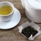 Фото зеленого чая в белой чашке с чайником