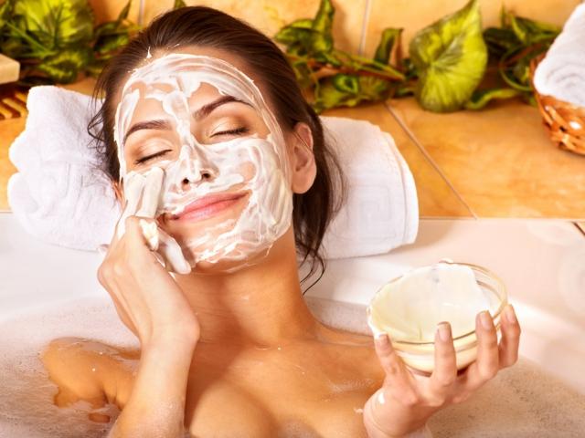 Фото девушки, которая наносит медово-сметанную маску на лицо
