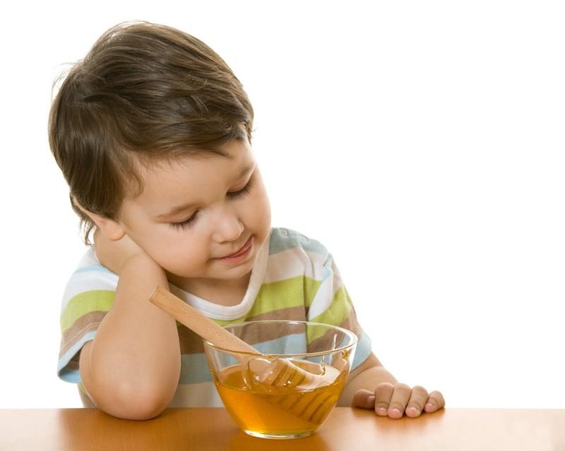 Фото ребенка за столом перед пиалой с медом