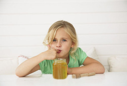 Фото девочки, которая кушает пчелиную сладость