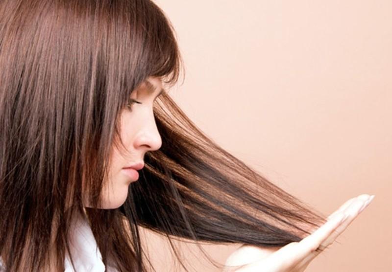 Девушка рассматривает секущиеся волосы