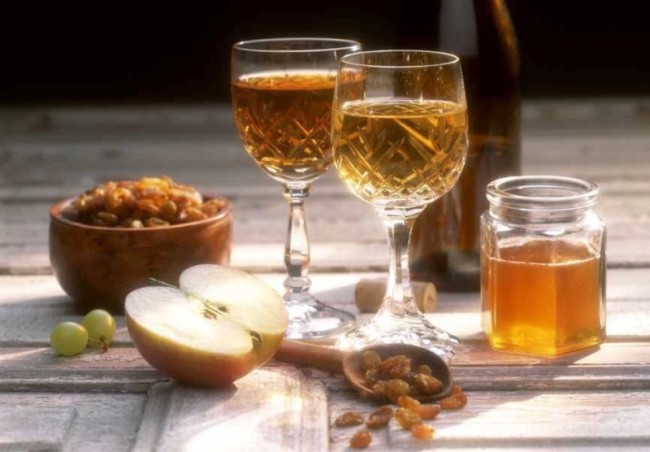 Медовуха в бокалах на фоне изюма, меда и яблока