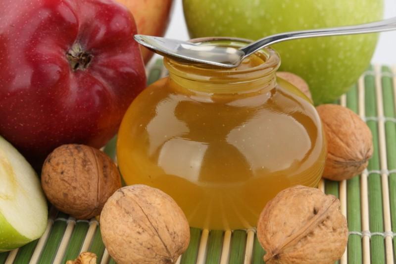 Мед в баночке на фоне яблок и орешков