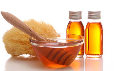 Мед в пиале и губка для проведения массажа