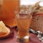 Рюмка с напитком на фоне меда и хлеба