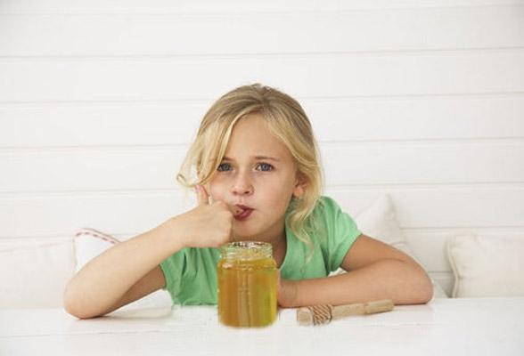 Девочка пробует мед из банки