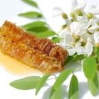 Акациевый мед в сотах на фоне цветков
