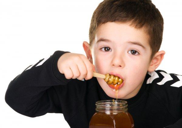 Мальчик кушает мед с ложечки