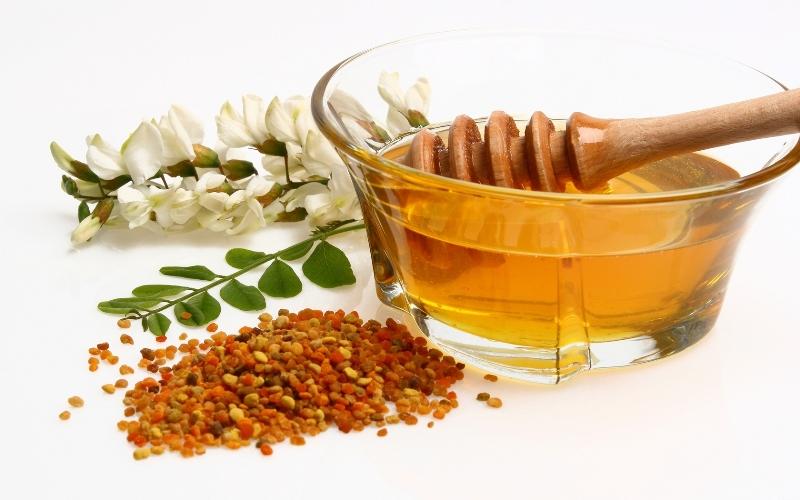 Пиалка с медом и пыльца на белом фоне