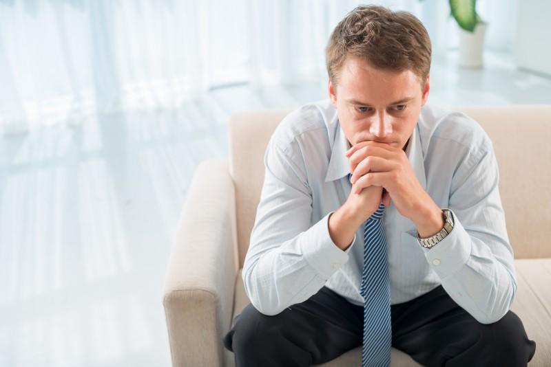 Задумчивый мужчина сидит на диване