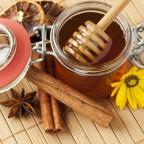 Баночка с медом и палочки корицы на столе