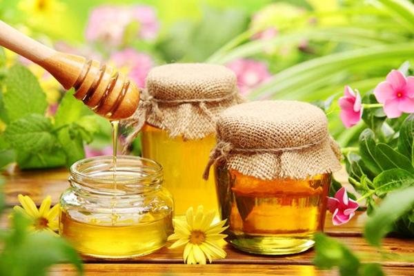 Три банки пчелиного продукта и цветы